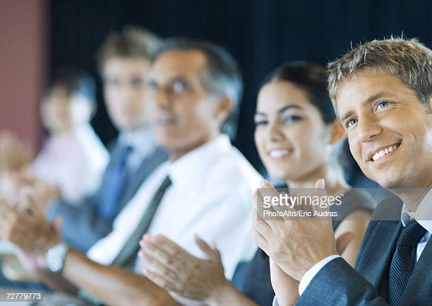 Executives sitting in seminar, clapping