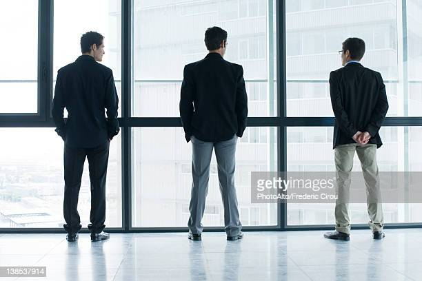 Executives standing side by side, looking out window