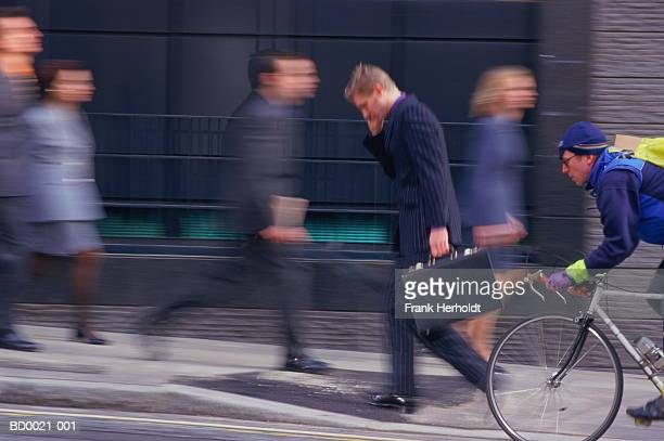 Executives walking on street,cycle courier passing by (blurred motion)