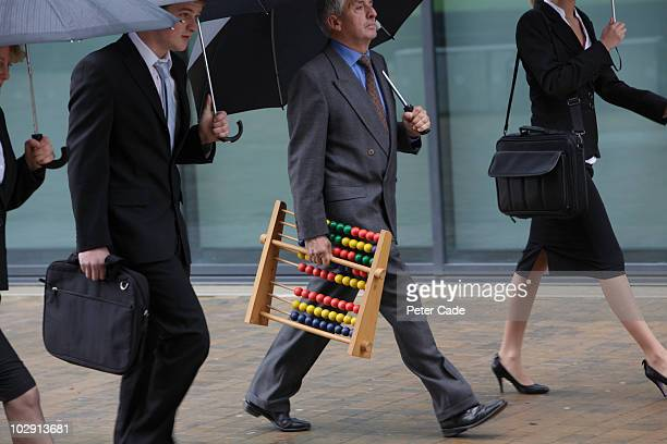 Executives walking, one with abacus