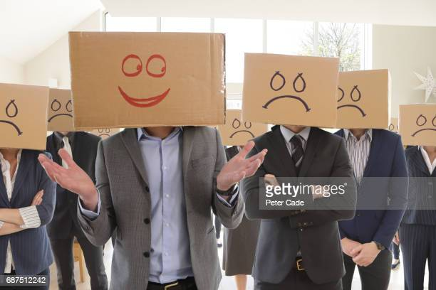 Executives with box heads, one happy, the rest sad