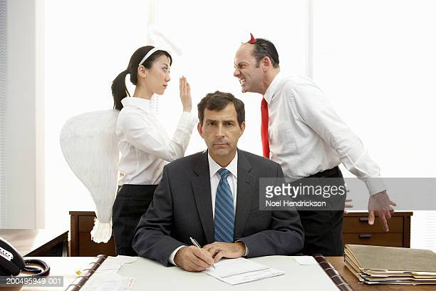 executives with halo and devil horns standing behind businessman - evil angel photos et images de collection