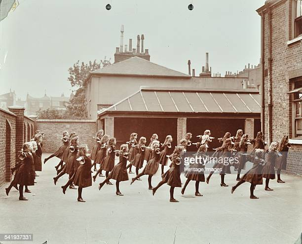 Exercise class Buckingham Street School Islington London 1906 A physical training drill in the playground with girls with legs raised backwards and...