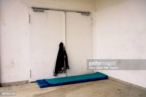 Exercise Mats By Jacket On Closed Doors In Abandoned Building