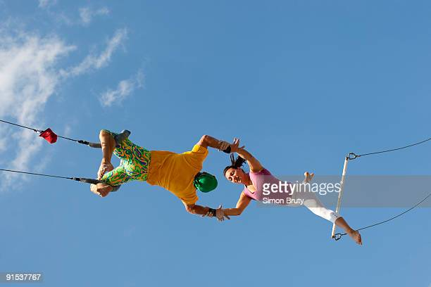 exercise on trapeze swings are popular - trapeze artist stock photos and pictures