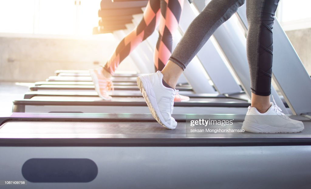 Exercise treadmill cardio running workout at fitness gym of woman taking weight loss with machine aerobic for slim and firm healthy in the morning.Show of running shoes, rubber floor, softness, : Stock Photo