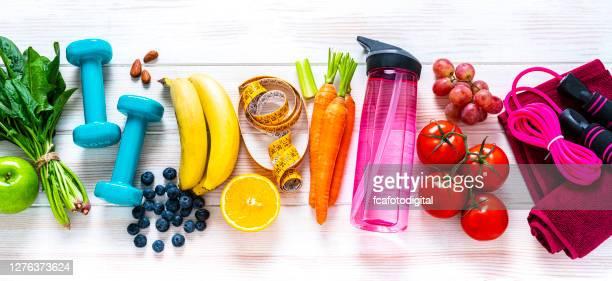 esercizio fisico e cibo sano: frutta colorata di raibow, verdure e articoli per il fitness - alimentazione sana foto e immagini stock