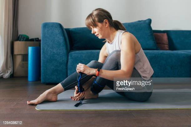 exercising at home: woman putting on ankle weights for a home workout - ankle stock pictures, royalty-free photos & images