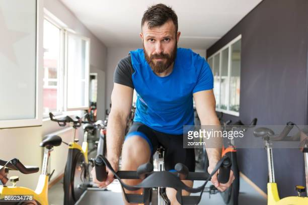 exercising class - exercise bike stock photos and pictures