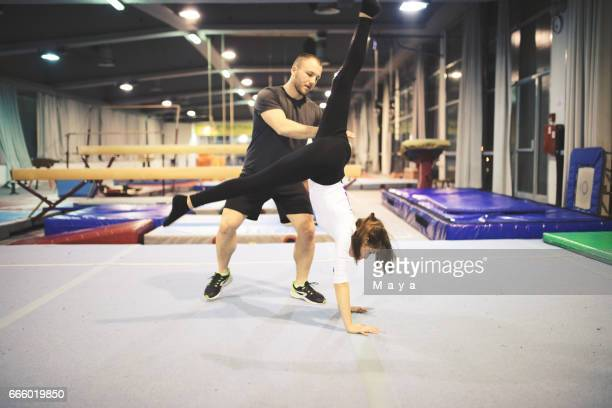 exercising gymnastic with trainer - school gymnastics stock photos and pictures