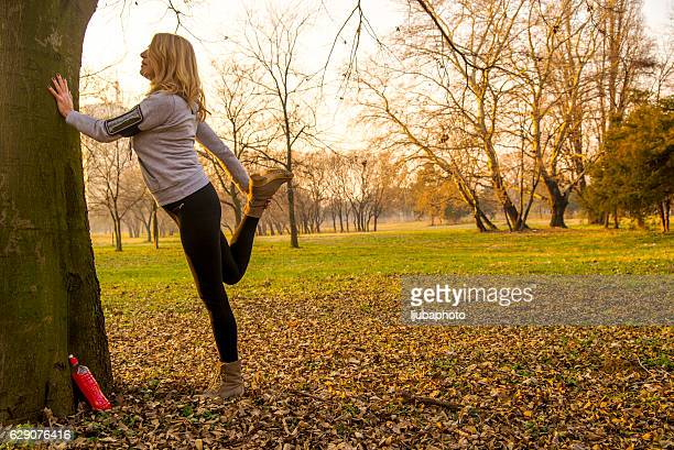 Exercising mature woman outdoors in autumn park during the day
