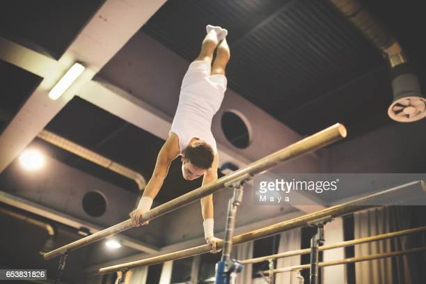 exercising on parallel bars. - parallel bars gymnastics equipment stock photos and pictures