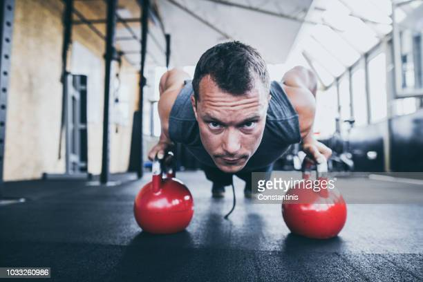 exercising with kettle bell in the gym - red kettle stock photos and pictures