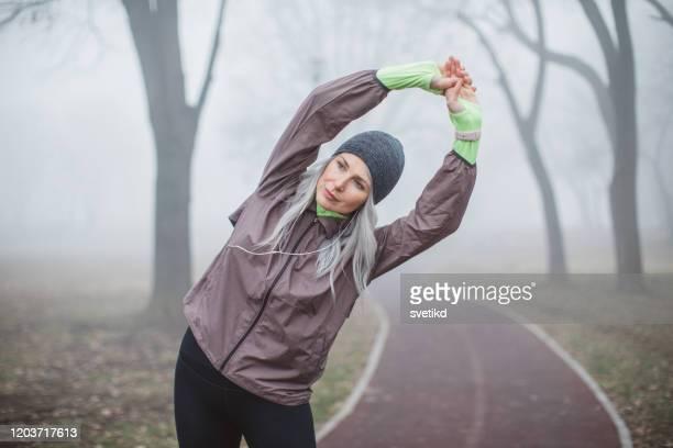 het uitoefenen van vrouw bij mistige dag - winter sport stockfoto's en -beelden
