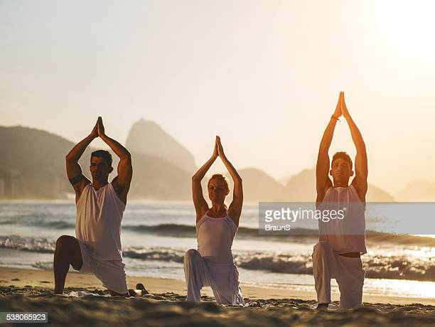 Exercising Yoga on the beach at sunset.