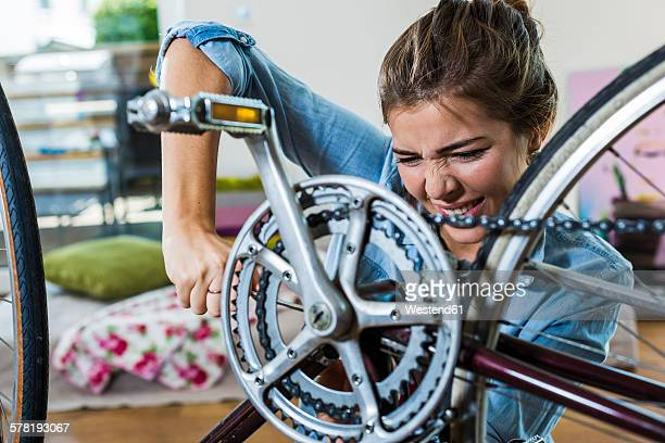 Exerted young woman at home repairing her bicycle