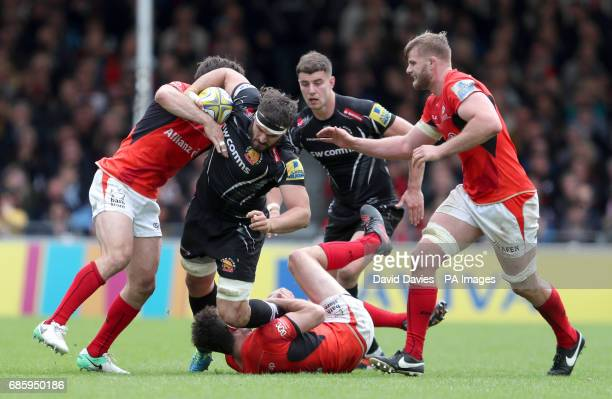 Exeter Chiefs' Don Armand is tackled by Saracens' Duncan Taylor and Marcelo Bosch during the Aviva Premiership Semi final match at Sandy Park, Exeter.