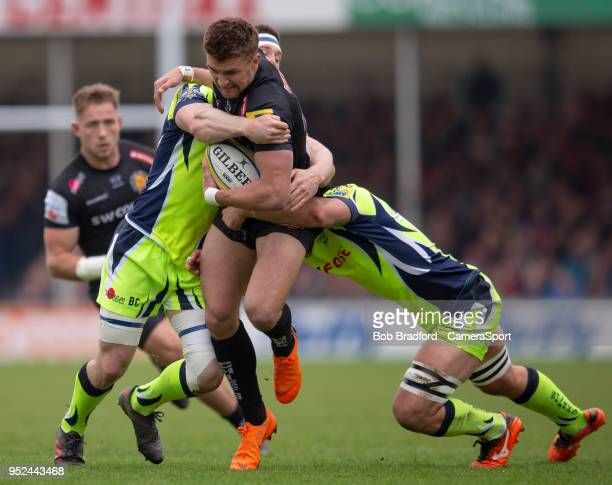 Exeter Chiefs' Henry Slade is tackled by Sale Sharks' Jonathan Ross and Ben Curry during the Aviva Premiership match between Exeter Chiefs and Sale...