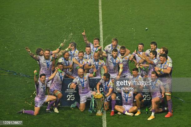 TOPSHOT Exeter Chiefs' players celebrate with the trophy on the pitch after the European Rugby Champions Cup final rugby union match between Exeter...
