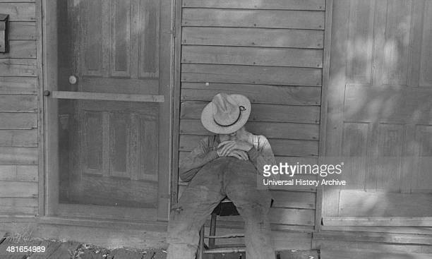 Exfarmer resting by a house in Circleville Ohio's Hooverville 1938
