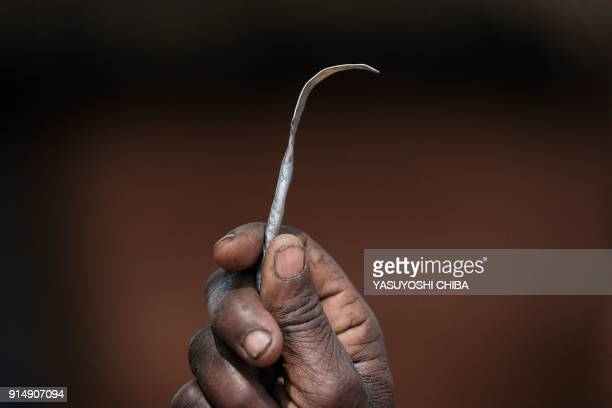 Exfemale genital mutilation cutter Monika Cheptilak who stopped practicing after the country set antiFGM law in 2010 shows a homemade tool from a...