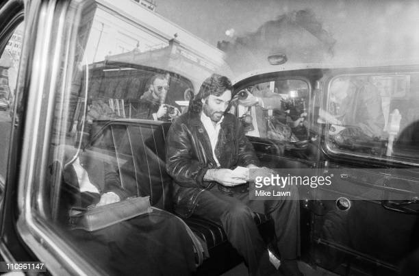Ex-footballer George Best sitting in the back of a taxi surrounded by press photographers, 5th November 1984.