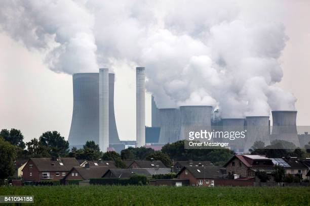 Exhaust rises from cooling towers at the RWE Niederaussem lignite coalfired power station with the houses in the village of Rate in the foreground in...