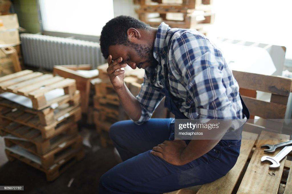 Empregado Africano exausto no armazém : Foto de stock