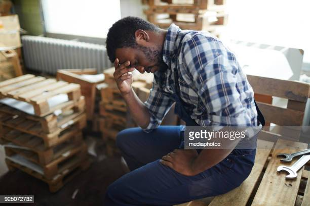 Exhausted African employee in warehouse