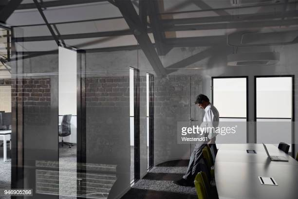 Exhausted and frustrated businessman standing in modern conference room