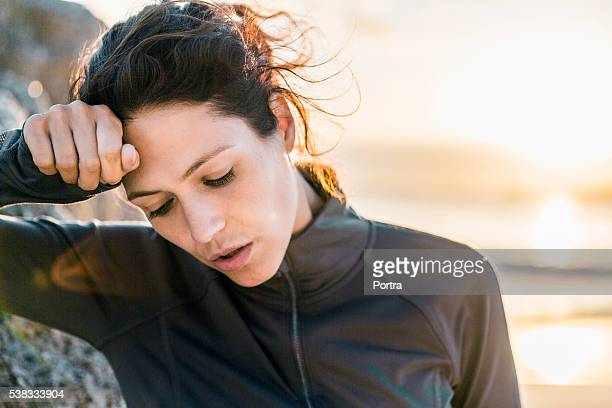 Exhausted athlete is wiping forehead at beach