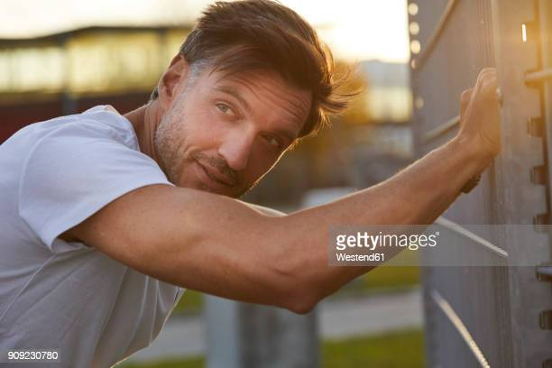 Exhausted athlete leaning against fence