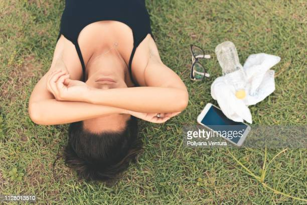 exhausted athlete lying on the grass - fainting stock pictures, royalty-free photos & images