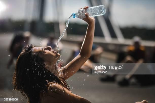 athlet gießt wasser auf sich selbst auf eine pause vom marathonrennen erschöpft. - durst stock-fotos und bilder