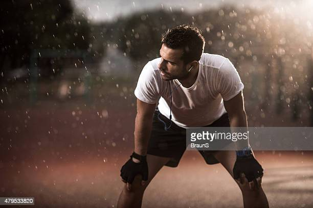 Exhausted athlete taking a breath after exercising on a rain.