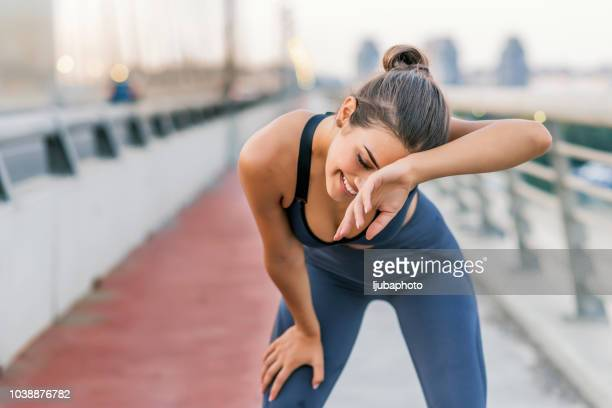 exhausted athlete taking a water break from sports training outdoors - bra top stock pictures, royalty-free photos & images