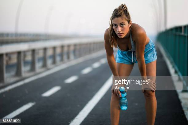 exhausted athlete taking a water break from sports training outdoors. - sportsperson stock pictures, royalty-free photos & images