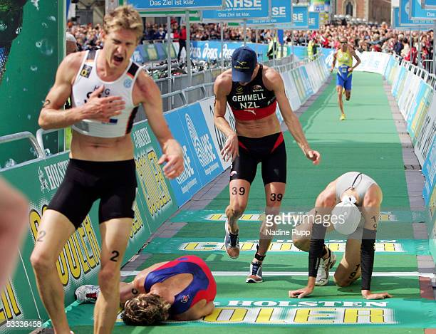 Exhausted athletes arrive at the finish during the Holsten City Man Elite Triathlon on August 7 2005 in Hamburg Germany