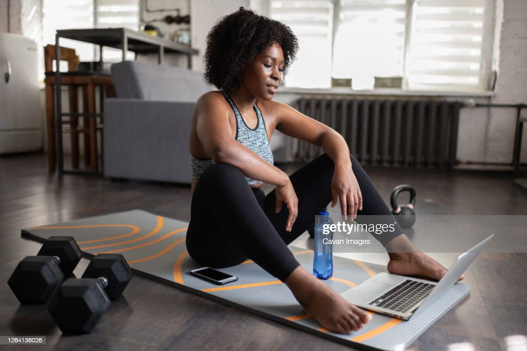Exhausted black athlete watching video : Stock Photo