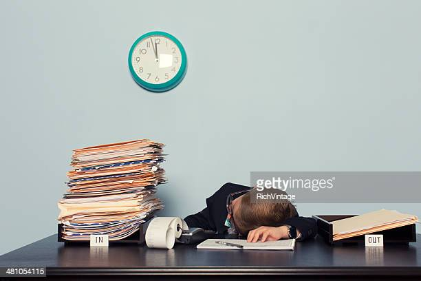 Exhausted Boy Businessman Lays on Office Desk