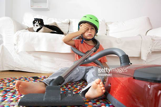 Exhausted boy in living room with cat and vacuum cleaner