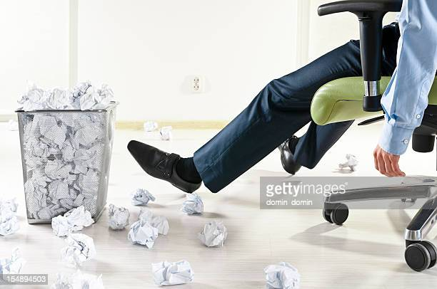 Exhausted businessman at the office, many crumpled paper balls