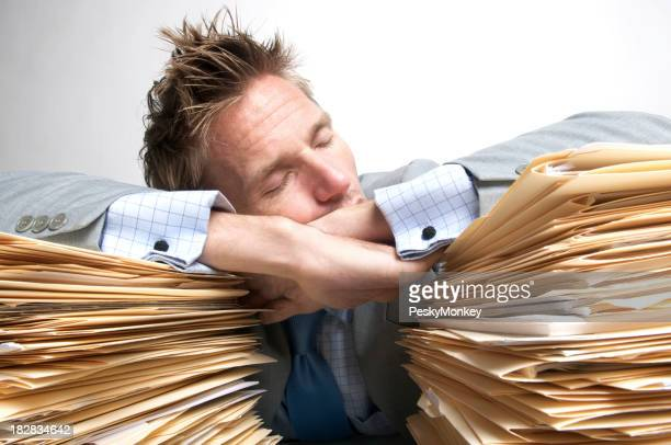 Exhausted Businessman Office Worker Snoozes on Pile of Files