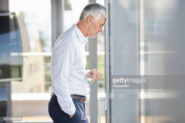 exhausted businessman resting head on windowpane - 敗北 ストックフォトと画像