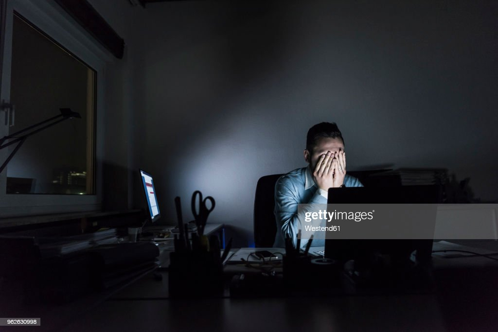 Exhausted businessman sitting at desk in office at night : Stock Photo