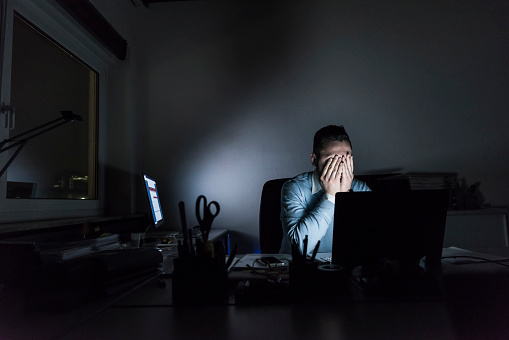 Exhausted businessman sitting at desk in office at night - gettyimageskorea