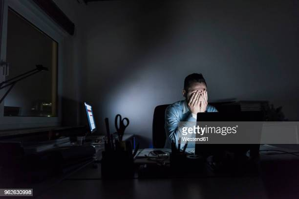 exhausted businessman sitting at desk in office at night - stress stock-fotos und bilder