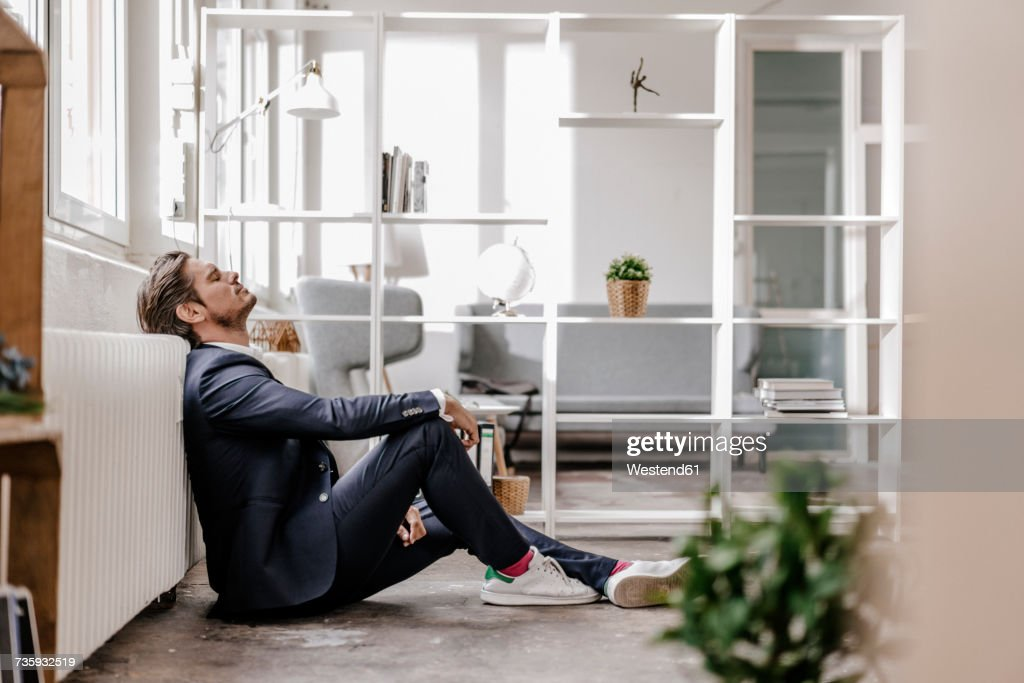 Exhausted businessman sitting on the floor : Stock Photo
