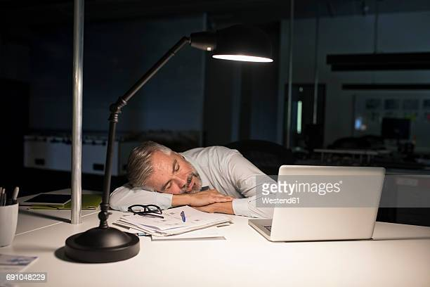 Exhausted businessman sleeping on office desk