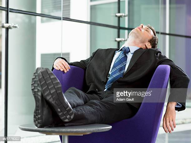 Exhausted Businessman Sleeps on an Armchair With His Feet Up on a Coffee Table
